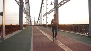 Full length of gorgeous fitness lade in sportswear running on modern pedestrian city bridge at sunset. Healthy active and slim senior woman jogging. Steadicam stabilized shot