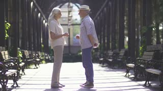 Full length of senior handsome man bending down on knee and proposing to beautiful fiancee with gray hair outdoors. Romance of engagement - male putting on diamond ring on the finger of senior fiancee