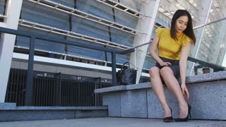 Full length of young asian business woman sitting on stairs near business centre, taking of high heeled shoes and rubbing her tired feet. Stressed business executive feeling pain cause of heel shoes