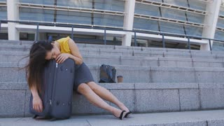 Full length of young asian business woman sleeping on suitcase outdoors near the airport during business trip. Tired exhausted corporate female taking nap after long working day during business travel