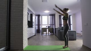 Full length of young fit attractive woman doing handstand near the wall at home. Morning exercise and gymnastics routine of slim mid adult female in sportswear. Healthy girl working out