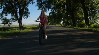 Full length shot of sporty cute teenage girl in glasses having fun riding bicycle in countryside. Blonde female teen cycling during sunset in summer on road among trees. Steadicam shot