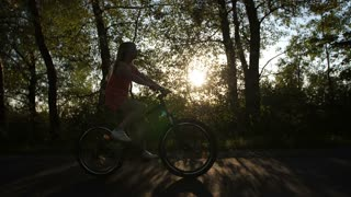 Full length shot of teenage girl on a bike enjoying beautiful sunset in countryside road in summer. Beautiful teen girl on bike trip feeling free and happy. Sun flare through the trees. Steadicam shot
