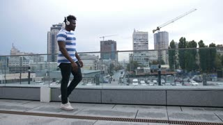 Funky african american dancer wearing white headphones, enjoying music and making dance moves on the street. Cheerful black male hipster performing moonwalk while dancing outdoors.