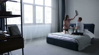 Funny couple fighting with pillows in the bed
