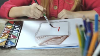 Girl painting with paintbrush and colorful paints