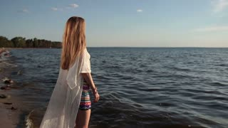 Girl takes deep breath enjoying fresh air on beach
