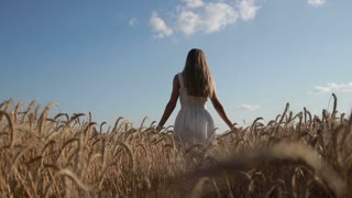 Girl with arms outstretched walking on wheat field