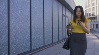 Gorgeous asian young female office worker having lunch break, walking with coffee to go and cellphone in hand. Attractive businesswoman using mobile phone while going to business office center.