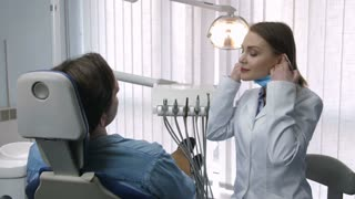 Gorgeous mid adult female dentist in white lab coat taking off protective face mask, looking and smiling at camera with confident radiant smile as her patient sits in dental chair at dental office