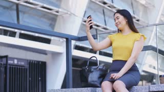 Gorgeous young asian business lady sitting near business center and making self-portrait photos on mobile phone to publish on social media. Attractive female in formalwear using cellphone for selfies