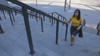 Gorgeous young asian business woman climbing stairs on business center stairway, in a hurry for work. Young female office employee going to job in the morning. Front view full length steadicam shot