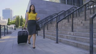 Gorgeous young business woman in pencil skirt and heeled shoes walking with travel suitcase to the airport on a summer day. Pretty female employee going on business trip travel with luggage.