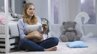 Gorgeous young pregnant woman sitting with healthy green smoothie jar on the carpet near bed in children's bedroom, caressing her belly, and smiling to camera with natural, candid and feminine smile.
