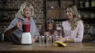 Grandmother pouring berry smoothie into mason jars