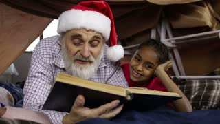 Grandpa with kids reading fairy tales on Xmas Eve