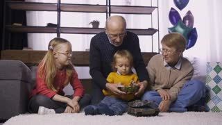 Grandparents sitting with grandchildren on the carpet in domestic room. Granddad teaching his cute toddler grandson to use remote radio controlled military tank toy, a present for birthday. Dolly shot