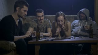 Group of four young drug addicts sitting at the table in home interior at night and snorting cocaine. Woman sniffs dope and passes rolled-up banknote to a man. Drug abuse, addiction, social issues
