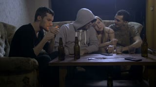 Group of four young drug addicts smoking cannabis at home at night on the sofa. One female and males passing marijuana joint to each other. Social issues, drug abuse and drug addiction concept