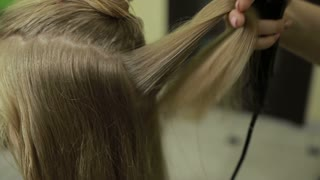 Hairstylist brushing long blonde hair of client
