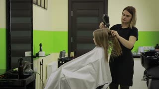 Hairstylist drying girl's hair with blow dryer