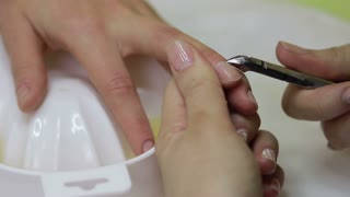 Hands removing cuticle with professional nail tool