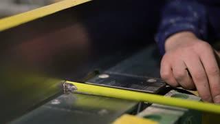 Hands with tape measuring frame on electric sander
