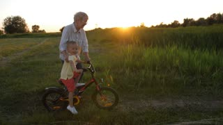 Handsome blonde toddler boy riding bicycle as grandmother giving him a helping hand in summer countryside during sunset. Excited grandson learning to cycle on bike. Steadicam shot.