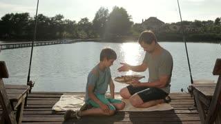 Handsome boy enjoying aroma of fried fish on lake