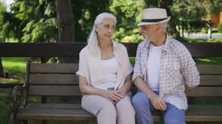 Handsome senior man with gray beard surprising his mature beautiful woman with white hair with marriage proposal while two sitting on a bench. Female with closed eyes getting engagement ring from man