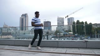 Handsome trendy african american hipster in white headphones walking along street and moving in afrohouse style dance over cityscape background. Cheerful black man dancing outdoors. Slo mo.