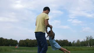 Happy asian father holding hands of his giggling little daughter and spinning her in circle in park against blue sky background. Cheerful dad playing with his lovely preschool girl outdoors.