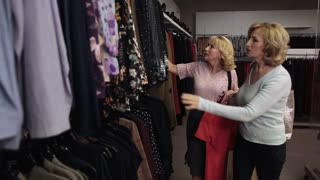 Happy blond women looking through clothes on rack