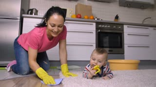 Happy cheerful hispanic mother and housewife scrubbing kitchen floor in rubber gloves at home. Adorable baby son crawling on carpet. Sweet family doing housework together. Slow motion. Dolly shot