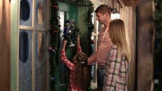 Happy family hanging Christmas wreath on the door