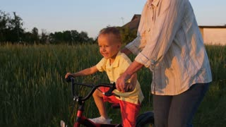 Happy first ride of little toddler boy on bicycle with grandmother's loving helping hand. Sweet blong grandsom learning riding bike while elderly grandmother assisting and teaching him during sunset