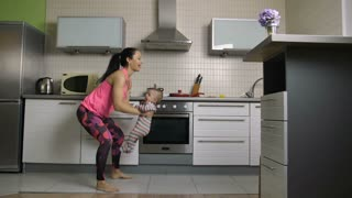 Happy fit mother doing squats lifting her baby boy at home in the kitchen. Sporty gorgeous female housewife making exercises together with her laughing infant child. Active family workout. Dolly shot.