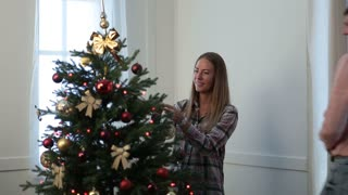 Happy married couple decorating Christmas tree