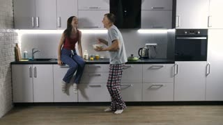 Happy morning of cheerful newlyweds couple. handsome young man inviting his wife to dance together in the kitchen as they cook breakfast. Joyful married couple in pajamas having fun