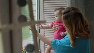 Happy mother with baby girl looking through window