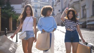 Happy multi ethnic young females walking in shopping center street, smiling and chatting together. Positive shopaholic women putting their shopping bags on shoulders while shopping with discounts