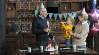 Happy multi-generation family celebrating little toddler grandson's birthday. Senior grandparents blowing horns with grandchildren and kissing their boy in decorated kitchen with baloons and cake.