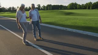 Happy retired couple having fun outdoors during a walk in countryside. Young at heart seniors with grey hair enjoying. Woman jumping and walking on road centerline holding husband's hand. Steadicam