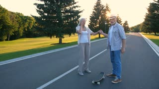 Happy retired couple having fun skateboarding in summer park. Beautiful aged woman with gray hair practiving and learning to skateboard while husband teaching her during sunset. Steadicam shot