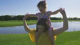 Happy toddler girl laughing and enjoying while riding on mother's shoulders with arms outstretched while mom running on green meadow in summer. Sweet daughter with down syndrome having fun with mom