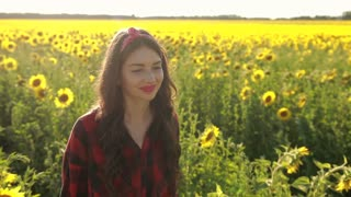 Happy woman walking in fresh sunflower field