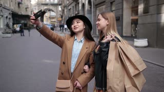 Happy women taking selfie after shopping on phone