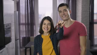Happy young adults married couple shaking new house keys in front of the camera and smiling. Boyfriend and girlfriend moving to new apartment together. Keys with wooden house shaped key ring.