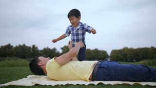Healthy lifestyle asian father exercising and playing with cute laughing little son, lifting him up in the air while lying on blanket on park lawn. Active dad having fun with preschool boy outdoors.