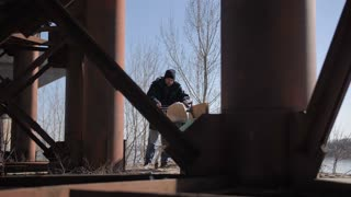 Homeless bearded man wallking under the bridge pushing shopping cart with his belongings on a cold autumn day. Beggar in jacket walking in city. Homelessness and social issues concept. Dolly shot